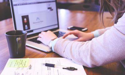 Mujer en el computador tramitando un certificado de tradición y libertad