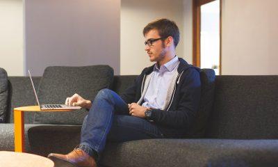Hombre joven sentado en un sofá, es un ejemplo de las comodidades de tener un trabajo freelance